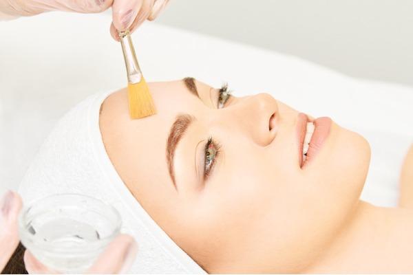 woman getting skin peel applied